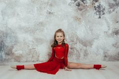 Girl gymnast in a red gymnastic swimsuit posing on studio background stock photos