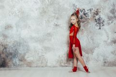Girl gymnast in a red gymnastic swimsuit posing on studio background royalty free stock image
