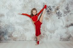 Girl gymnast in a red gymnastic swimsuit posing on studio background stock image
