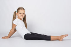 Girl gymnast sitting on the floor with legs stretched and leaned back on his hands Royalty Free Stock Images