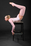 Girl gymnast took graceful pose at chair Royalty Free Stock Image