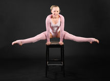 Girl gymnast took graceful pose at stool. Girl gymnast wearing in pink suit took graceful pose at stool in black studio Stock Image