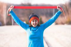 Girl with a gymnastic band. A woman is doing exercises on the street. Morning gymnastics. Training with a rubber band. Workout in winter Royalty Free Stock Images