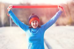 Girl with a gymnastic band. A woman is doing exercises on the street. Morning gymnastics. Training with a rubber band. Workout in winter Stock Images