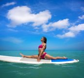 Girl gymnastics on paddle surf board SUP royalty free stock photo