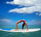 Girl gymnastics on paddle surf board SUP. In summer yoga royalty free stock image