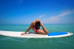 Girl gymnastics on paddle surf board SUP stock images