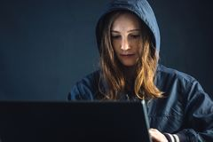 Girl hacker uses a laptop to hack the system. Creation and infection of malicious virus. Girl hacker uses a laptop to hack the system. Stealing personal data royalty free stock photo