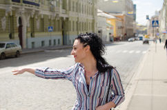 Girl hailing to the taxi Stock Photography