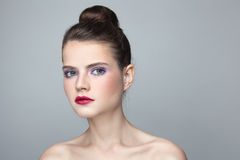 Girl with hair bun. Portrait of young beautiful woman with stylish make-up and hair bun Royalty Free Stock Photography