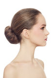 Girl with hair bun. Profile portrait of young beautiful girl with hair bun over white background royalty free stock photos