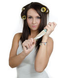 Girl with hair curlers. Young woman with hair curlers holding newspaper Stock Photo