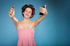Girl in hair curlers applying red lipstick Stock Photos