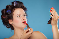 Girl in hair curlers applying red lipstick Stock Photography