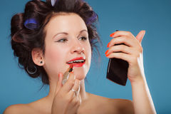Girl in hair curlers applying red lipstick Royalty Free Stock Images