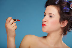 Girl in hair curlers applying red lipstick royalty free stock photos