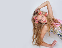 Girl with hair curlers on a long fair hair Stock Image