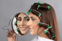 Girl with hair curlers and mirror Stock Image