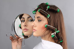 Girl with hair curlers and mirror Royalty Free Stock Image