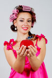 The girl in hair curlers with a red apple in her hand. gray background Royalty Free Stock Photo
