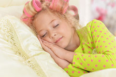 Girl in hair curlers sleeping in her bed Royalty Free Stock Images
