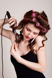 Girl with hair curlers talking on the phone and makes the hairstyle Royalty Free Stock Photography