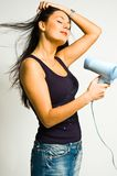 The girl with the hair dryer. The beautiful girl with the hair dryer stock image