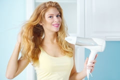 Girl with hair dryer. On light stock images