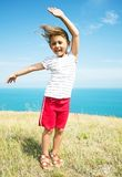 Girl with hair fluttering in the wind. Is in the yellow grass against the blue of the sea Stock Photography