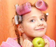 Girl, hairdo,apple,curlers. Girl in a pink housecoat, with curlers in the head and the apple of her face, isolated on orange background Royalty Free Stock Images
