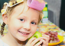 Girl, hairdo,apple,curlers. Girl  housecoat, with curlers in the head and the apple of her face Stock Photos