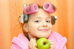 Girl, hairdo,apple,curlers. Girl in a pink housecoat, with curlers in the head and the apple of her face, isolated on orange background Stock Photos