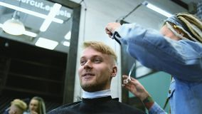 The barber cuts a bearded man with scissors in the salon. Girl hairdresser cuts scissors bearded man in the salon stock video