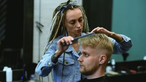 The barber cuts a bearded man with scissors in the salon. Girl hairdresser cuts scissors bearded man in the salon stock video footage