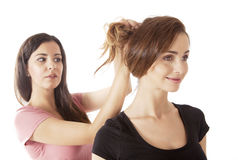 Girl at hairdresser. Pretty women at hairdresser trying new hairstyle perhaps, with hairdresser in background Stock Photo