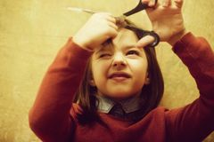Girl shutting eye from fear while cutting hair. Girl, hairdresser, small, little child shutting eye from fear while cutting long, brunette, hair with metallic royalty free stock photo