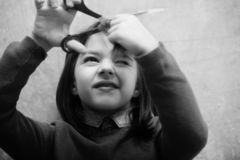 Girl shutting eye from fear while cutting hair. Girl, hairdresser, small, little child shutting eye from fear while cutting long, brunette, hair with metallic royalty free stock images