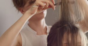 Girl hairdresser-stylist in white shirt with short stylish hairstyle combs her hair and makes festive hairstyle to sitting girl. stock video