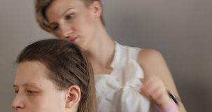 Girl hairdresser-stylist in white shirt with short stylish hairstyle combs her hair and makes festive hairstyle to sitting girl. stock footage