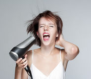 Girl with hairdryer Stock Images