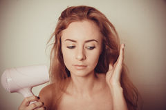 Girl with hairdryer Royalty Free Stock Images