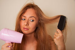 Girl with hairdryer Royalty Free Stock Photos