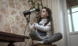 Girl with hairdryer. Royalty Free Stock Photo