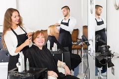 Girl hairstylist doing haircut mature person Royalty Free Stock Photography