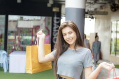 Girl shopping in department store. Girl half blood ethnic German-Thai go shopping with happy and smile on face and holding paper bag in a department store Royalty Free Stock Photos