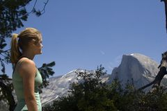 Girl at Half Dome. Young woman  looking at Half Dome in Yosemite in the Sierra Nevada mountains of California Royalty Free Stock Photo
