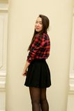 Girl half-turned to the camera. In red shirt and black skirt royalty free stock images