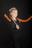 Girl in halloween costume with magic wand on black background Royalty Free Stock Images