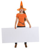 Girl in Halloween hat holding blank billboard Royalty Free Stock Photos