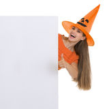 Girl in Halloween hat showing blank billboard Stock Images